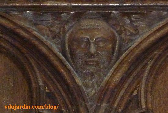 Stalles de la cathédrale de Poitiers, dosseret, tête barbue dans une capuche avec des feuilles