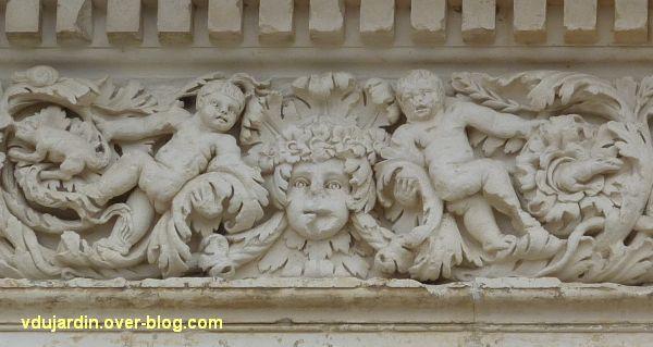 Poitiers, façade de Saint-Jean-de-Montierneuf, 8, deux putti encadrant un masque