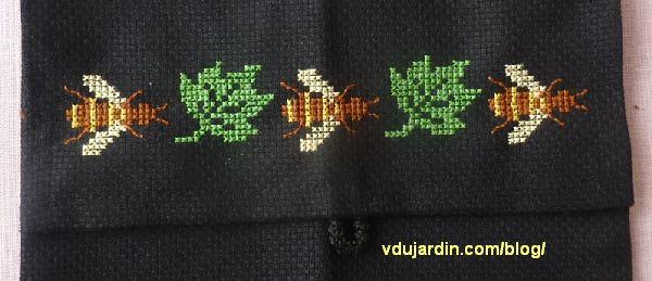 Une pochette en toile Aïda noire avec trois abeilles et deux feuilles, détail de la broderie