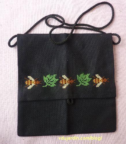 Une pochette en toile Aïda noire avec trois abeilles et deux feuilles, l'ensemble
