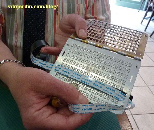 Olivier avec son poinçon et sa plaque Braille, détail de la plaque